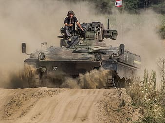 Man in black and red jacket riding on battle tank