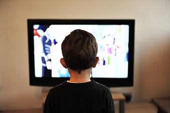 Boy standing in front TV turned on