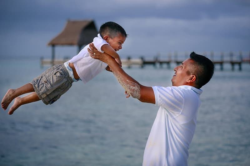 Shallow focus photography of man carrying his son on beach during day time