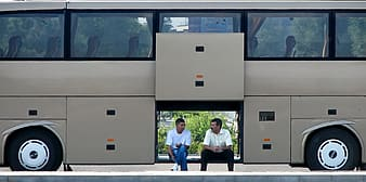Two men sitting on bus compartment