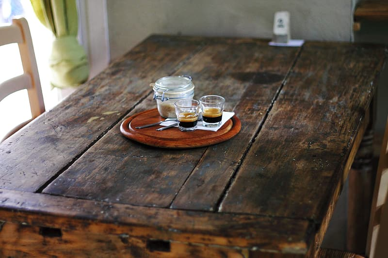 Two shot glasses beside mason jar on round brown wooden tray