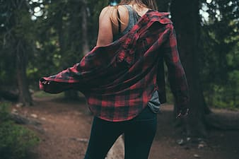Woman in red and black plaid long sleeve shirt and black pants standing in forest during