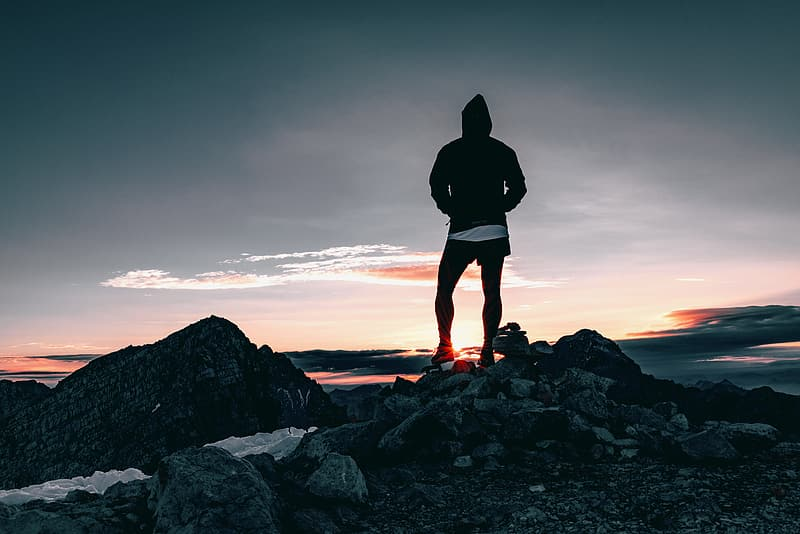 Man standing on stone during sunset