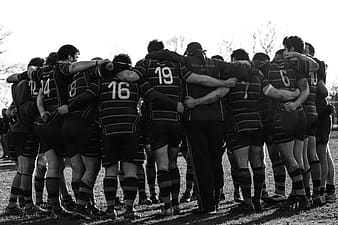Grayscale photography of group of men in huddle