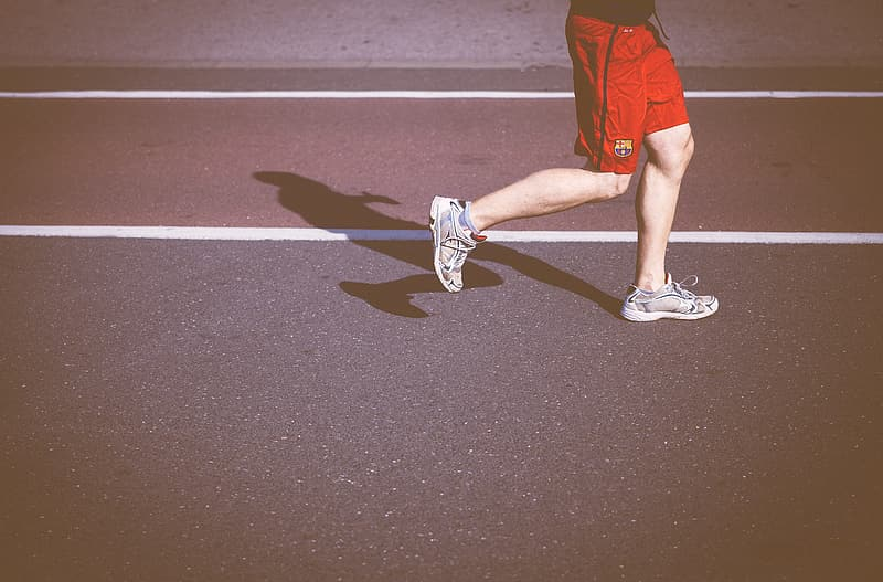 Person wears white running shoes while jogging