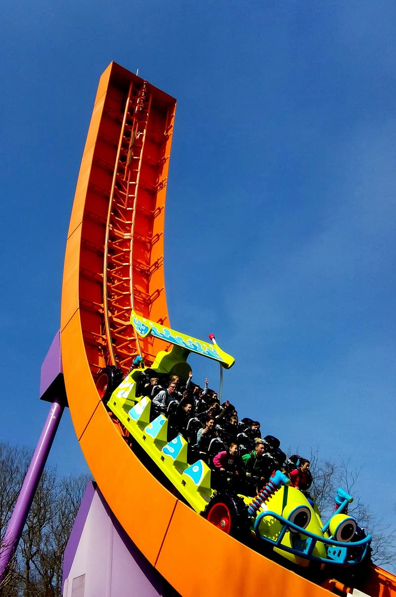 People sitting on yellow and red roller coaster during daytime
