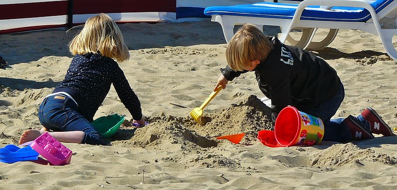 Two children crawling on sand