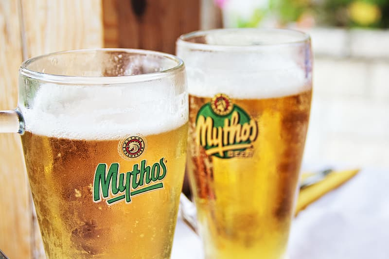 Two clear Mythos drinking glass filled with beer