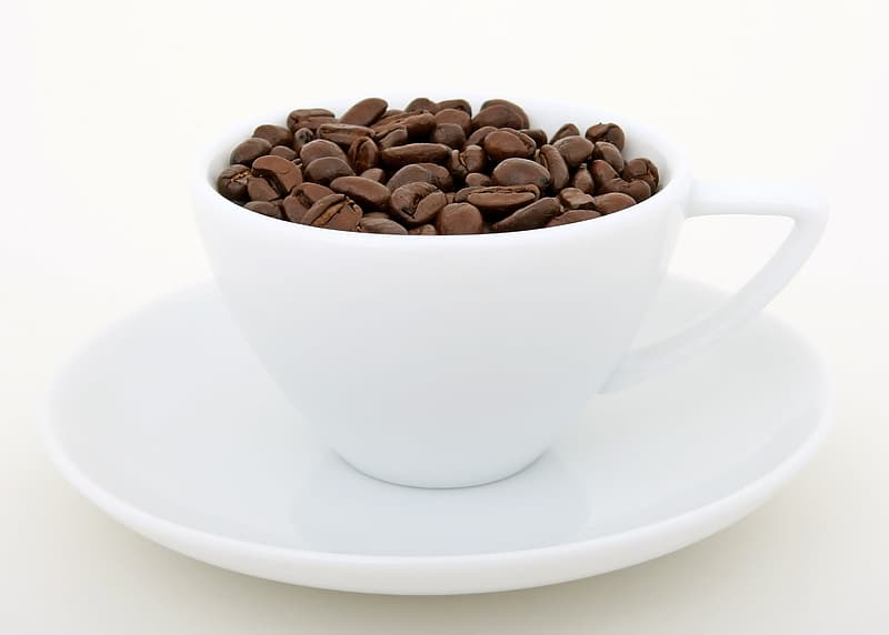 Coffee beans on white ceramic coffee cup and saucer