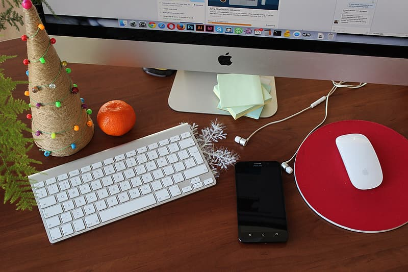 Black android smartphone beside apple magic mouse and apple wireless keyboard and silver imac