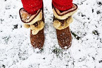 Person wearing brown suede mid-calf mukluk boots at snow