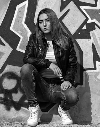 Woman in black leather jacket and blue denim jeans sitting on the floor