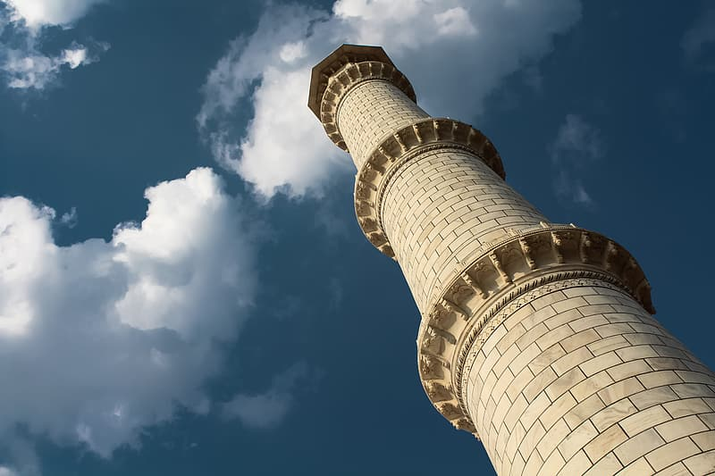 Low-angle photography of beige concrete lighthouse tower under blue and white sky