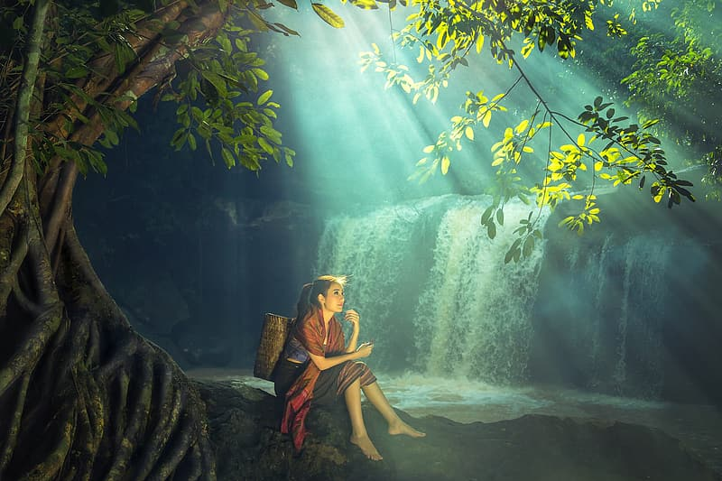 Woman in yellow dress sitting on rock in front of waterfalls