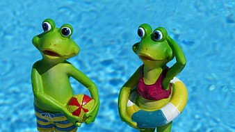 Two green frog near body of water figurines