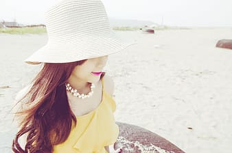 Photography of sitting woman wearing summer hat during daytime