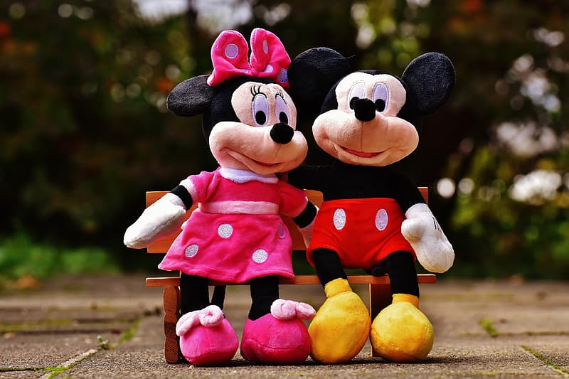Minnie Mouse and Mickey Mouse sitting on bench plush toys