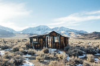 Brown wooden house near snow covered mountain during daytime