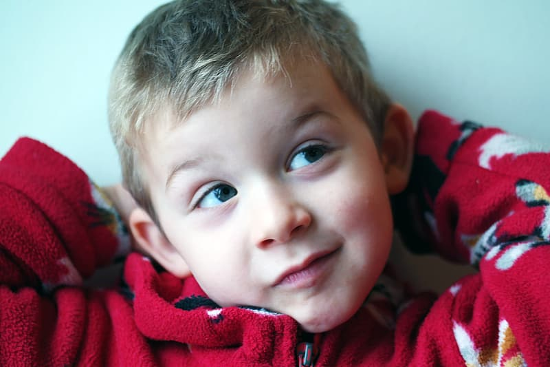 Selective focus photography of boy in red hoodie grinning