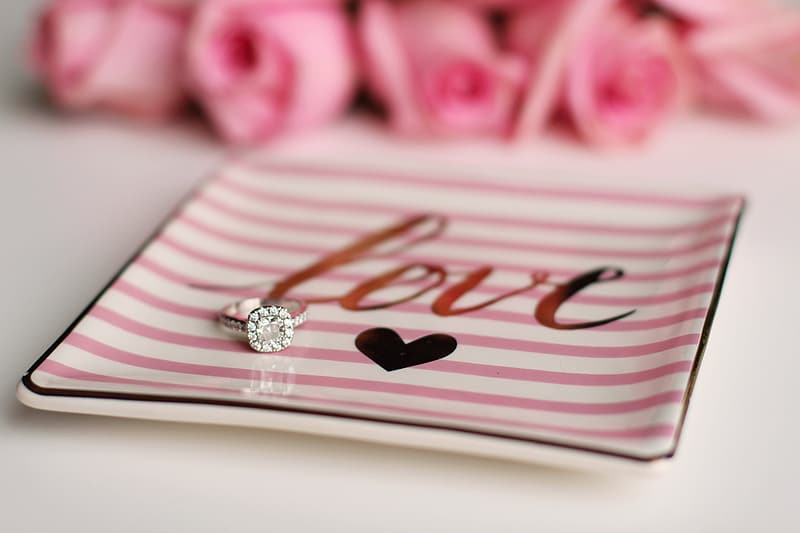 Silver-colored ring with clear gemstone on square pink plate