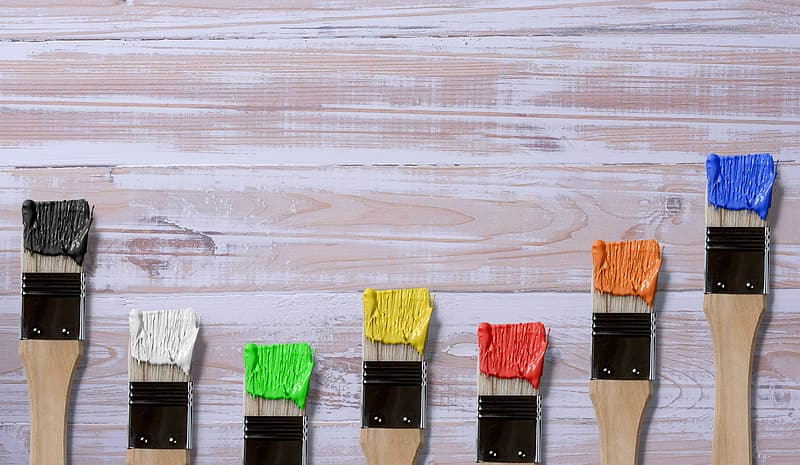 Seven brown-and-black paint brushes with assorted-color paints