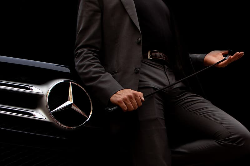 Person in gray suit holding black and silver mercedes benz steering wheel