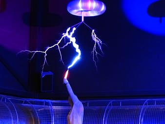 Person holding orange tool with lightning effect above ceiling