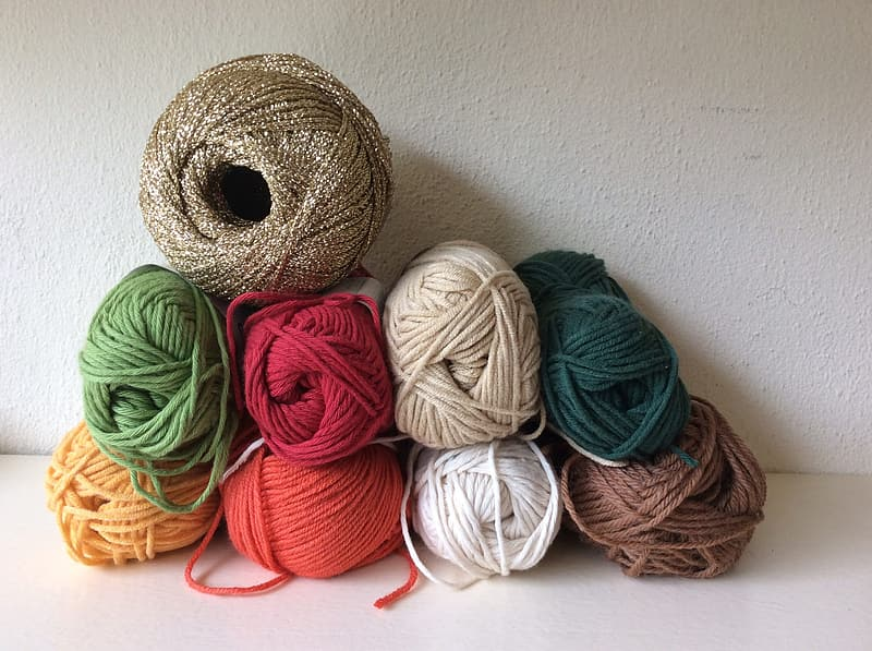 Assorted-color yarn lot on top of white surface