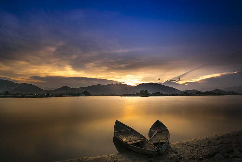 Two boats on seashore across mountain during golden hour