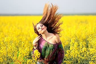 Woman wearing purple and green off-shoulder top in yellow rapeseed flower field