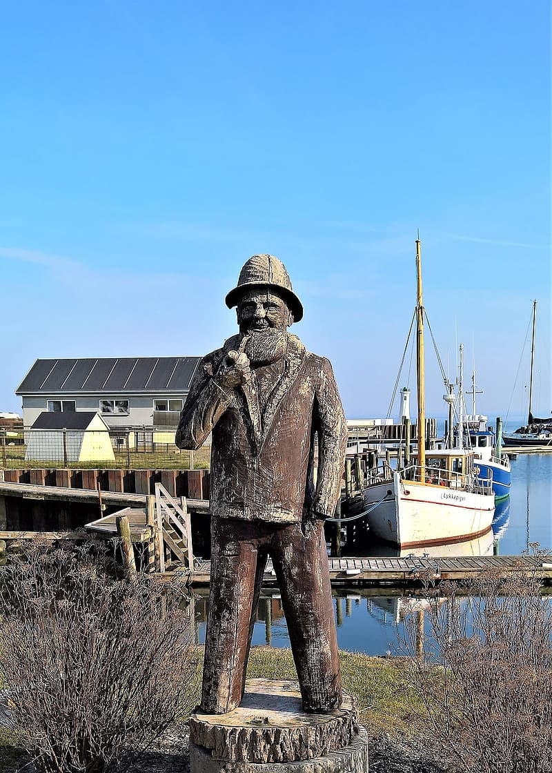 Man statue near body of water during daytime