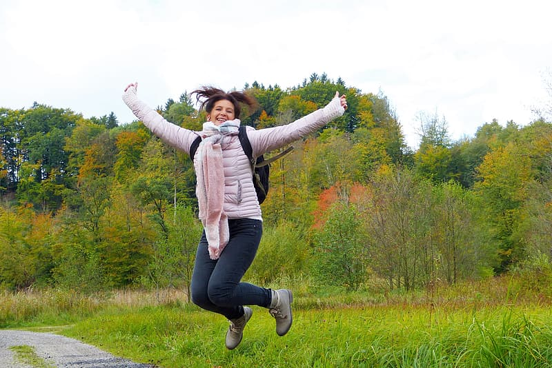 Woman wearing jacket and blue denim jeans jumping