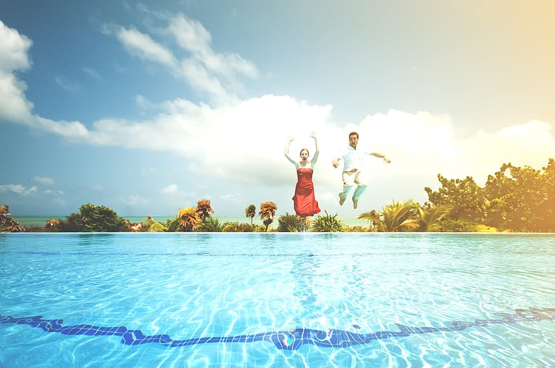 Man and woman jumping on pool during daytime