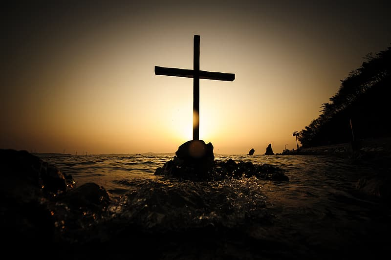 Silhouette photo of cross in the middle of ocean