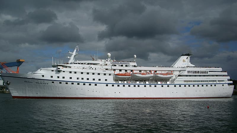 White cruise ship on sea under gray clouds