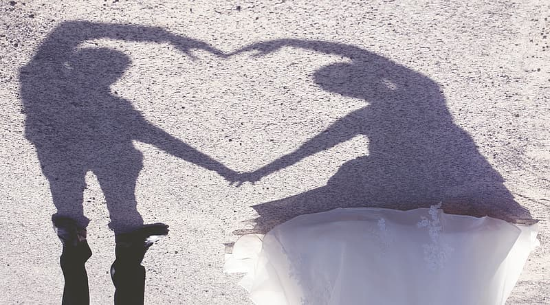 Man and woman forming heart shadow