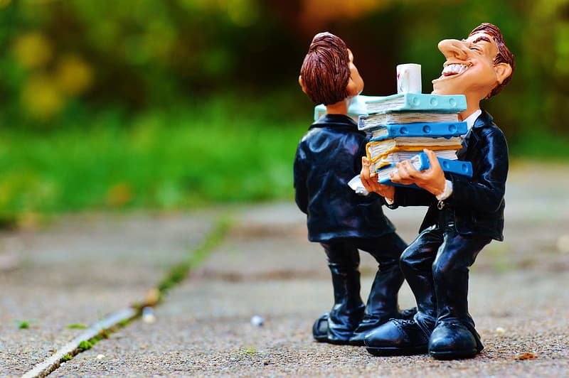 Two figurines of man carrying stack of books