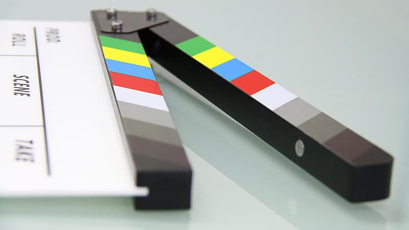 White and black clapperboard on white glass surface
