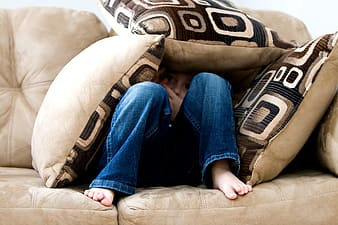 Person wearing blue jeans hiding under throw pillows