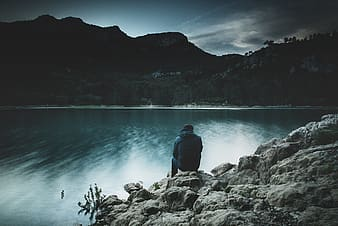 Man in blue jacket sitting on rock near body of water during daytime