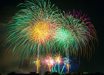 Green, purple, and yellow fireworks photo during nighttime