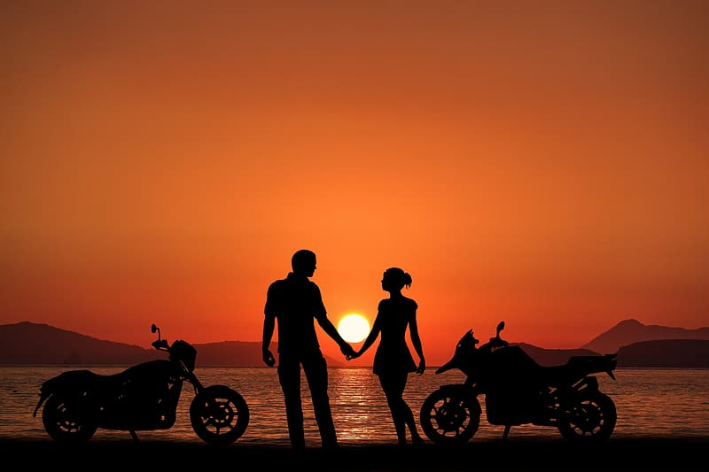 Silhouette of 2 person standing beside motorcycle during sunset