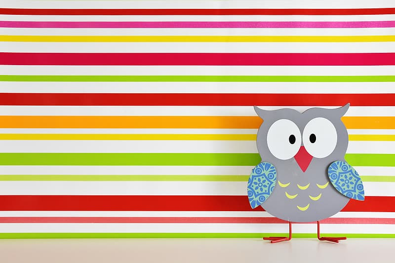 Gray owl cutout decor standing near multicolored striped wall