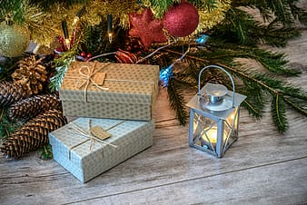Two grey gift boxes beside grey candle lantern and pinecones