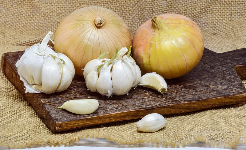 White garlic on brown wooden chopping board