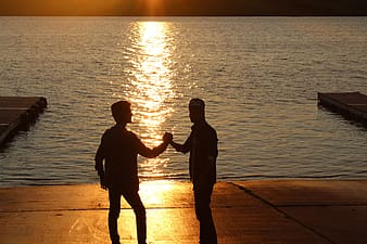 Two standing man holding hands near ocean during sunset