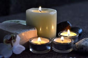 Four lighted candles in candle holders