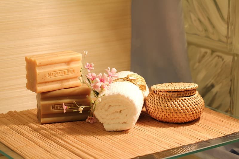 Two soap bars near white face towel and brown basket on brown wooden table