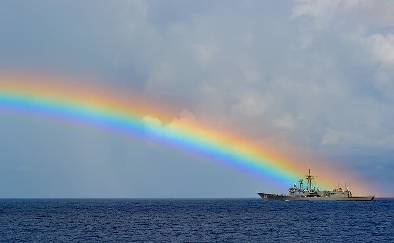 Sailing ship on rippling body of water under rainbow