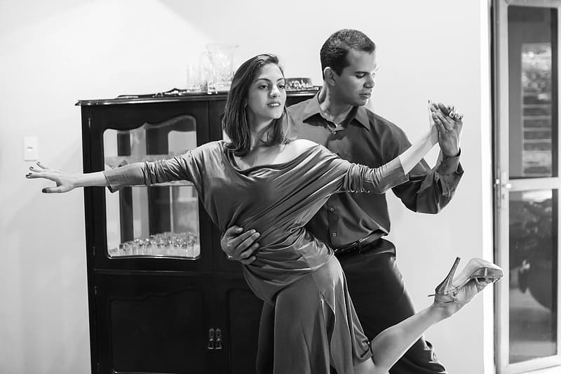 Grayscale photo of man and woman dancing